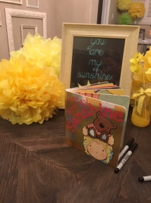"Guests were encouraged to write a special note for the baby in the ""You are my Sunshine"" book."