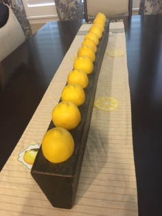Use your ordinary home decor items to your advantage when hosting. The candles were removed from this wooden holder, and lemons added to the theme.