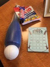 "Shower game was ""Baby All-star Bingo."" Guests filled their own Bingo cards with gifts predicted to be unwrapped. THe first one with a bing won the prize (a baseball bat and ball, Baby Ruth bar and sunflower seeds)."