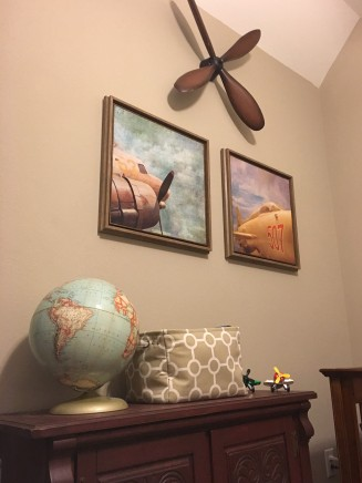 "A replica of a vintage propeller creates a nice focal point, which will eventually be centered above the ""big boy"" bed when transitioned out of the crib. Two prints of vintage planes add a touch of color and coordinate well with the vintage globe (from Mom's childhood). The furniture piece was purchased and replainted from Goodwill and provides lots fo storage for extra linens (crib sheets, waterproof mattress pads and blankets)."